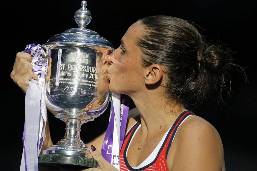 Kei Nishikori strumming the trophy, after winning the Memphis Open; a gleeful Martin Klizan punching the air after beating Gael Monfils in the Rotterdam World Tennis final; (above) Roberta Vinci kissing the trophy after her triumph in the in the inau