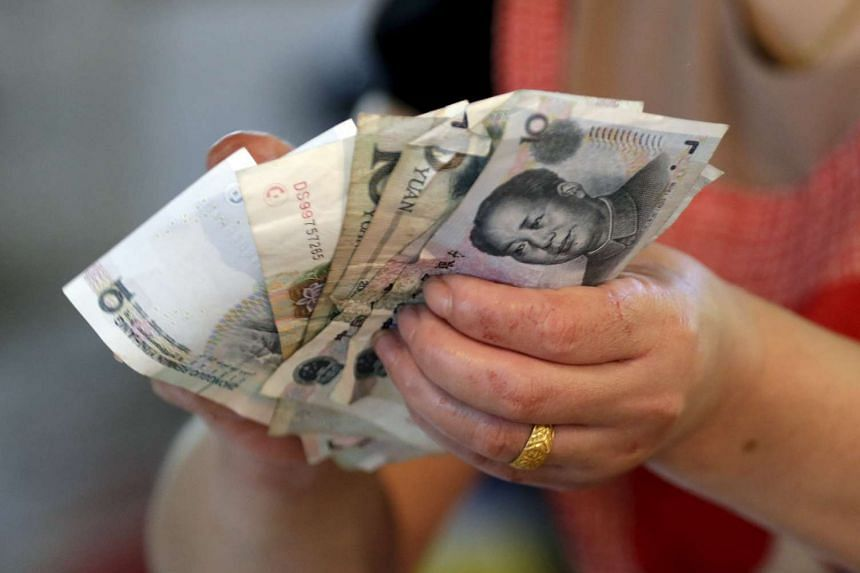 A vendor holds Chinese Yuan notes at a market in Beijing, China.