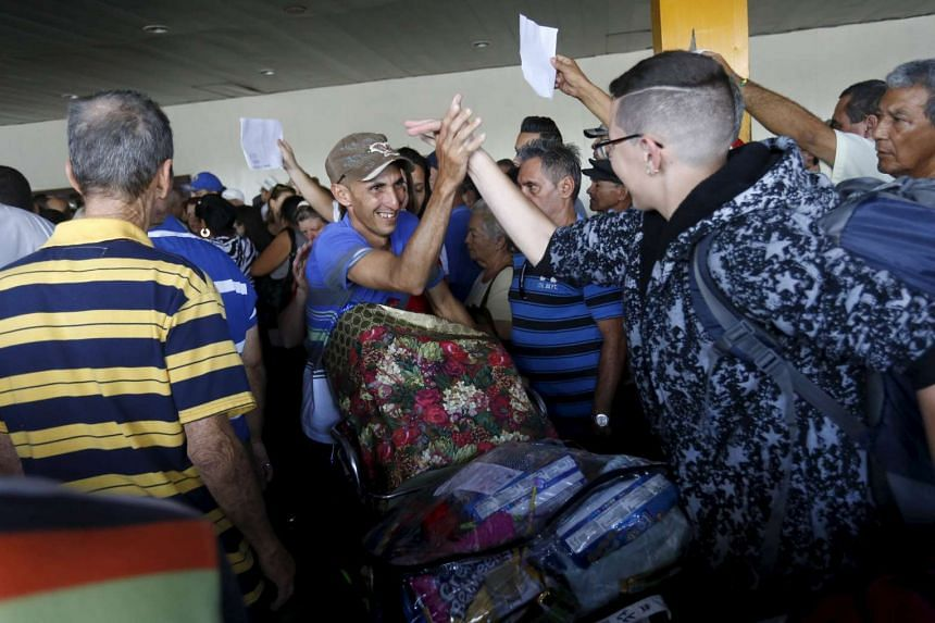 A man is greeted by relatives while he arrives from the US at Jose Marti International Airport in Havana on Dec 17, 2015. The United States and Cuba have agreed to restore scheduled commercial airline service for the first time in more than five deca