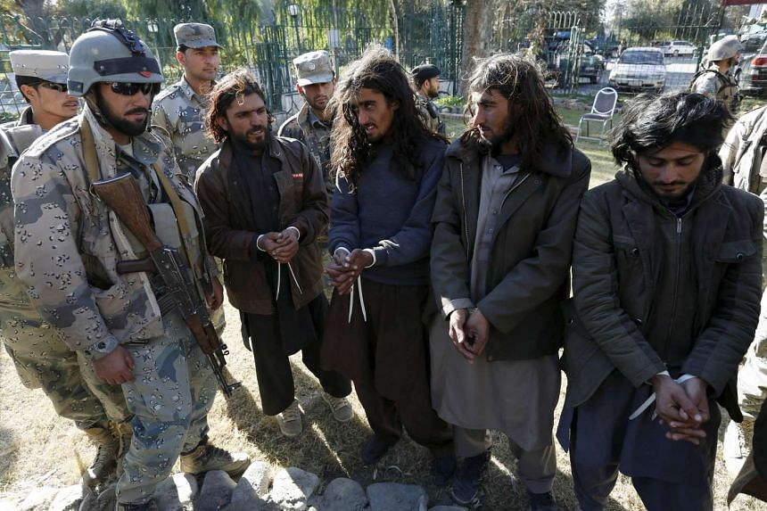 Taleban militants arrested by the Afghan border police standing during a presentation of seized weapons and equipment in Jalalabad on Dec 29, 2015.