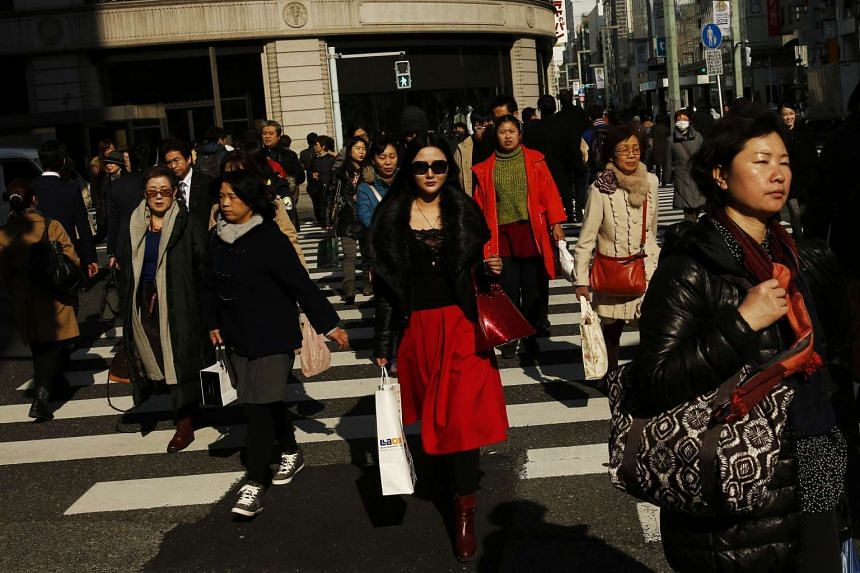 People crossing a street in the shopping district of Ginza in Tokyo, Japan.