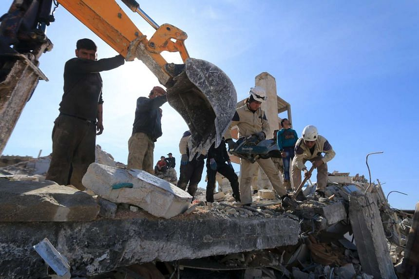People and Civil Defense members remove rubble while looking for survivors in the ruins of a destroyed Medecins Sans Frontieres (MSF) supported hospital hit by missiles in Marat Numan, Idlib province, Syria, on Feb 16, 2016.