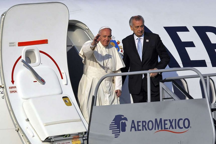 Pope Francis waves upon landing at Francisco J. Mujica airport in Morelia, Michoacan State, Mexico on Feb 16, 2016.