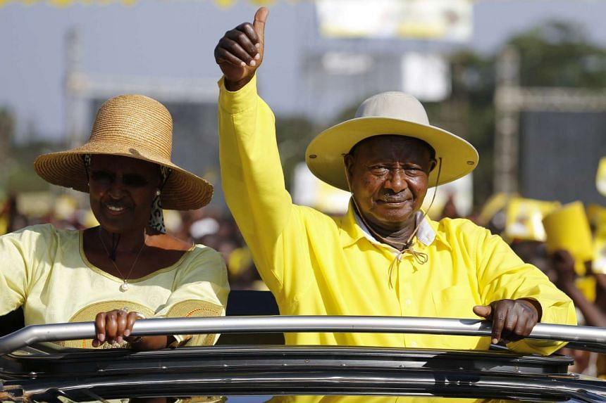 Uganda's incumbent President Yoweri Museveni (right) greets his supporters upon his arrival at his last campaing rally on Feb 16, 2016.