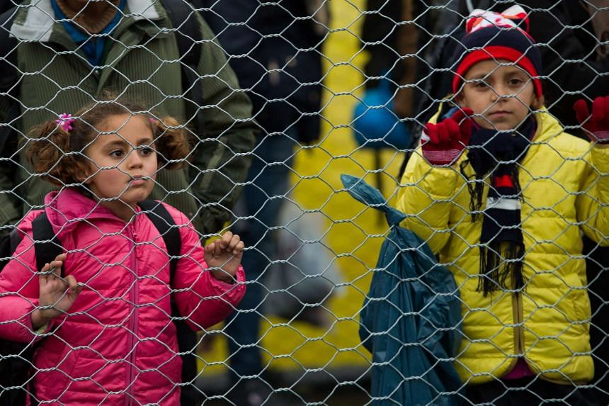 Refugees and migrants children walk along a border fence after they crossed the Slovenian-Austrian border near the village of Spielfeld, Austria on Feb 16, 2016.