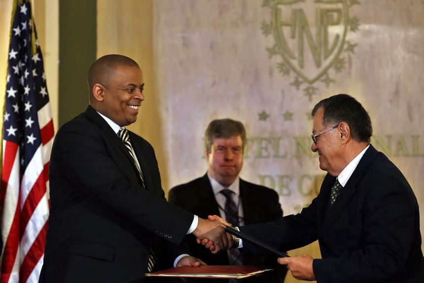 US Secretary of Transportation Anthony R. Foxx (left) and Cuba's Transportation Minister Adel Yzquierdo exchange signed documents of a memorandum of understanding between USA and Cuba.