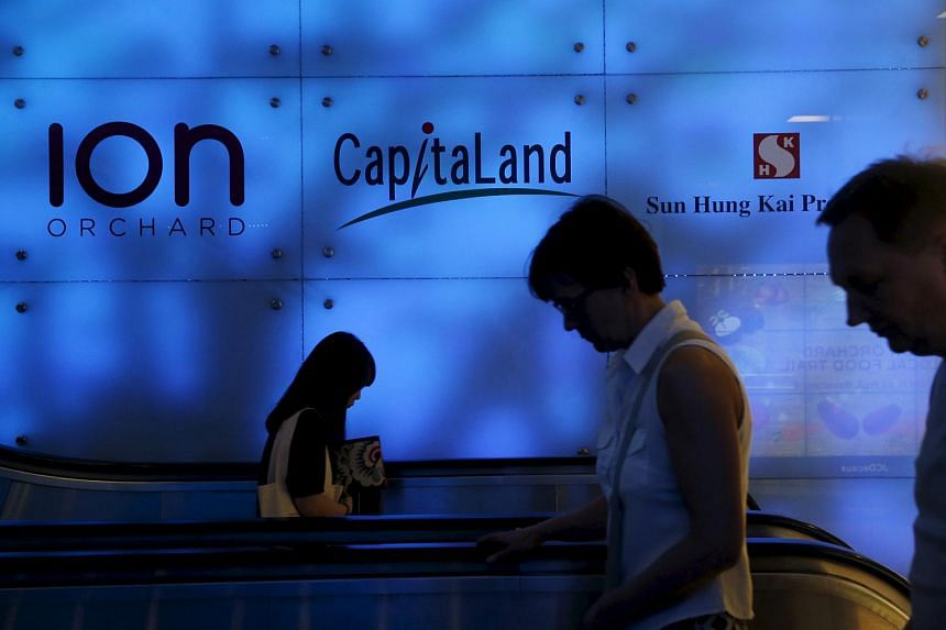People pass a CapitaLand logo at a mall in Singapore.