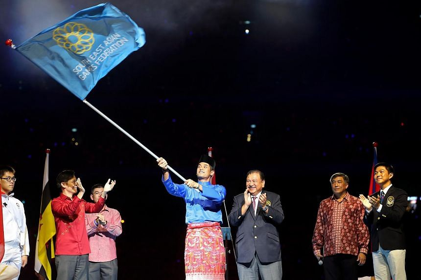 Malaysia's Youth and Sports Minister Khairy Jamaluddin waving the SEA Games Federation flag at the closing of the 28th SEA Games in Singapore.