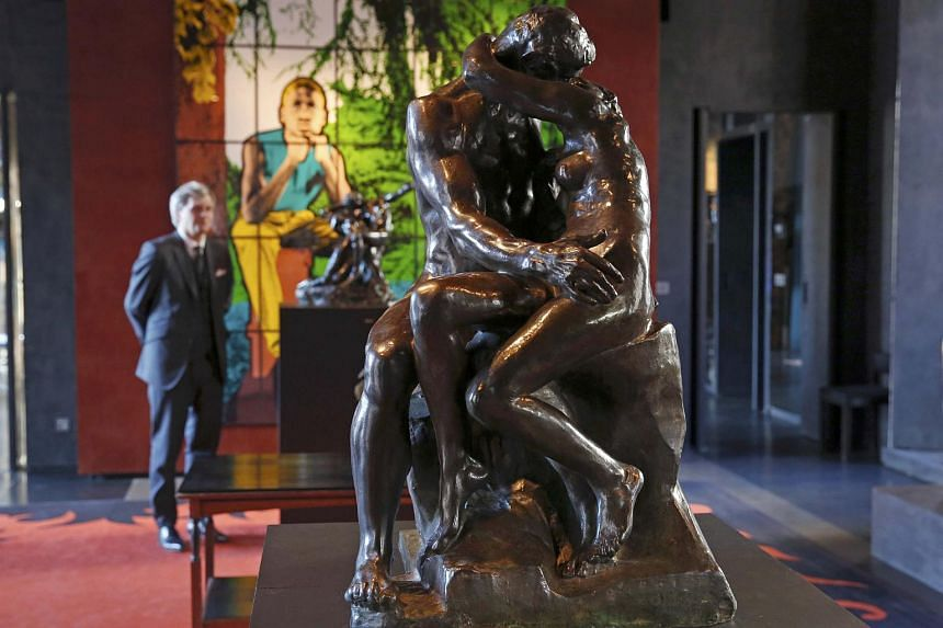 Auctioneer Alexandre Giquello looks at Le Baiser (the Kiss), part of a sale of five bronzes by French sculptor Auguste Rodin.