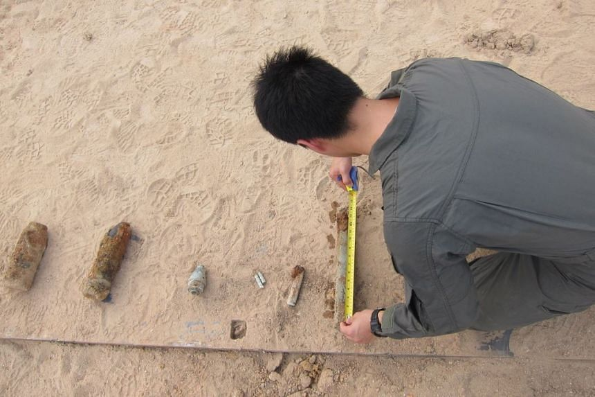 A member of SAF's Explosive Ordnance Disposal team assessing the relics.