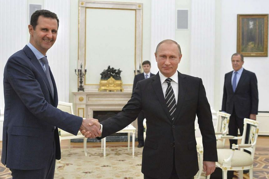 Russian President Vladimir Putin (right) shakes hands with Syrian President Bashar al-Assad during a meeting on Oct 20, 2015.