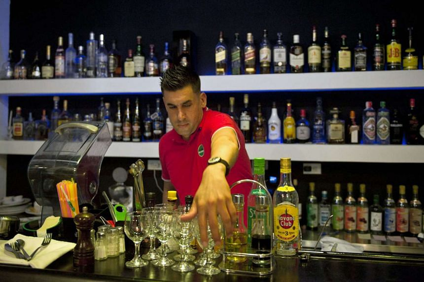 A bartender prepares the glasses on the bar of a private restaurant in Havana, Cuba.