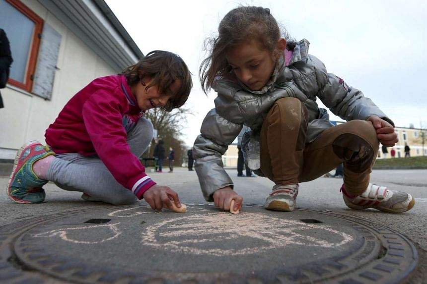 Refugee children using chalk to draw on the ground at a refugee deportation registry centre in Germany.