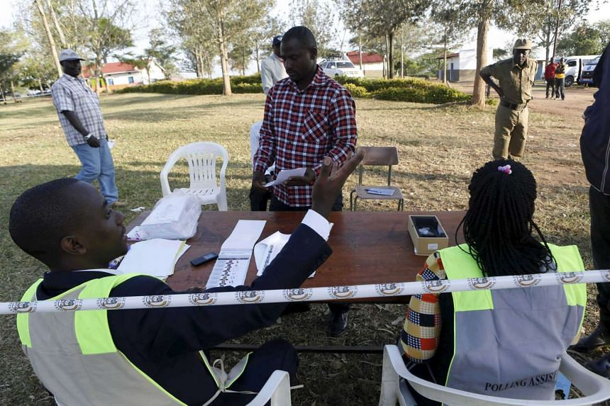 A polling assistant verifies a voter's identity at a polling station during elections in Kirihura, Uganda on Feb 18, 2016.