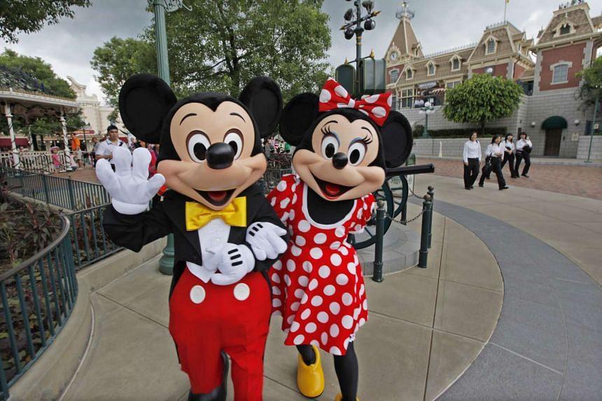 Actors clad as cartoon characters Mickey Mouse and Minnie Mouse at Hong Kong Disneyland Resort.