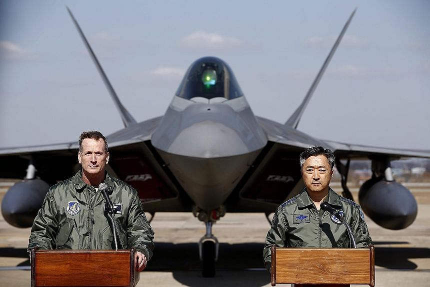 Lt-Gen O'Shaughnessy (left) of the US Air Force and South Korean Air Force operations commander Lee Wang Geun in front of an F-22 stealth fighter during a press briefing at Osan Air Base yesterday.