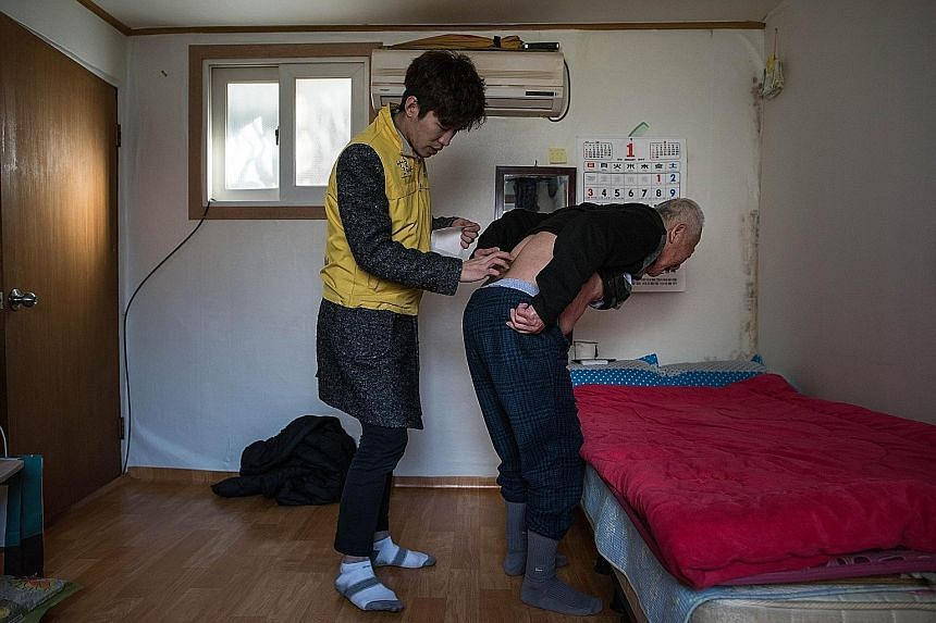 An elderly South Korean getting some help applying a heating pad in his one-room flat in Seoul. A new report says the number of single-person households in South Korea last year was about 5.06 million, a 7.7-fold surge from 661,000 in 1985.