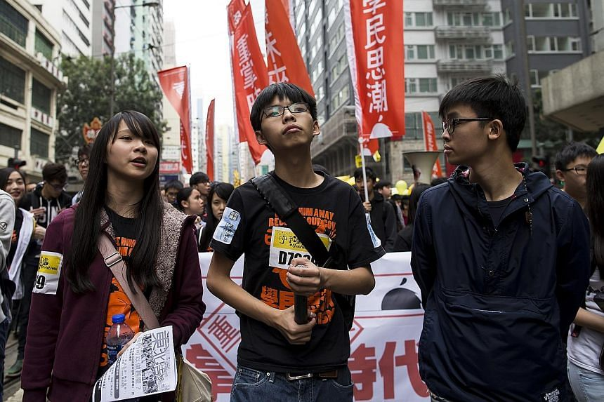 Hong Kong student leaders (from left) Agnes Chow, Joshua Wong and Oscar Lai marching to demand universal suffrage during a rally last year. Mr Lai, 21, and several other members of the student activist group Scholarism will run in local legislative p