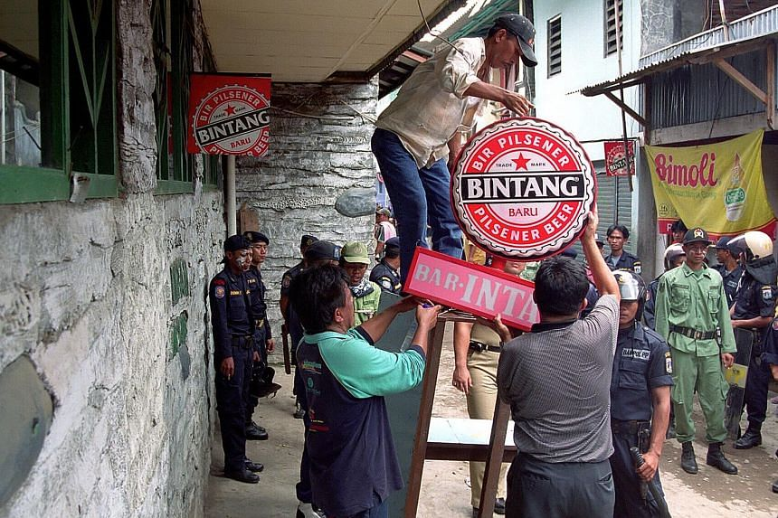 Government workers removing a beer advertisement in front of a brothel in the Kalijodo red-light district. The Jakarta administration is pushing forward with a plan to clean up the area and relocate some 300 residents.