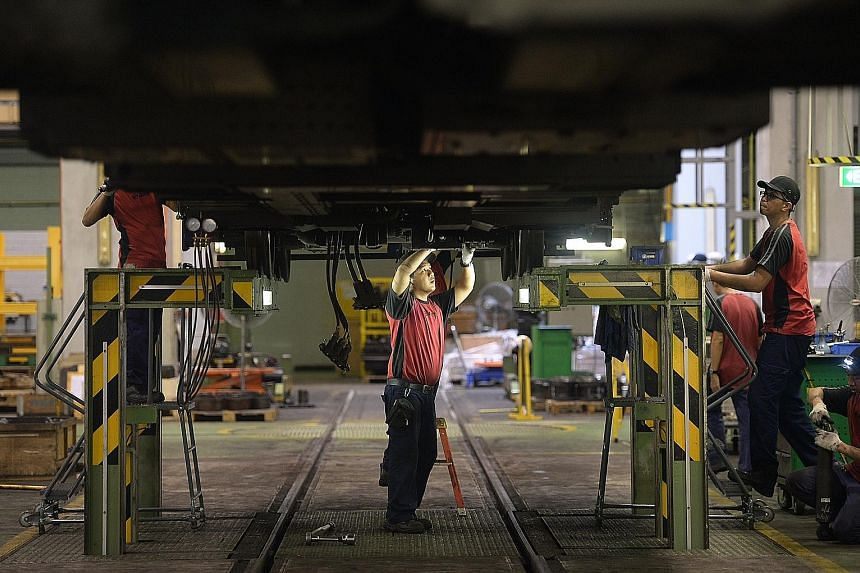 Staff at SMRT's Kim Chuan Depot working on trains yesterday. SMRT says 70 per cent of staff bonuses is tied to operational key performance indicators, and this will be raised to 80 per cent with the new team-based incentives.
