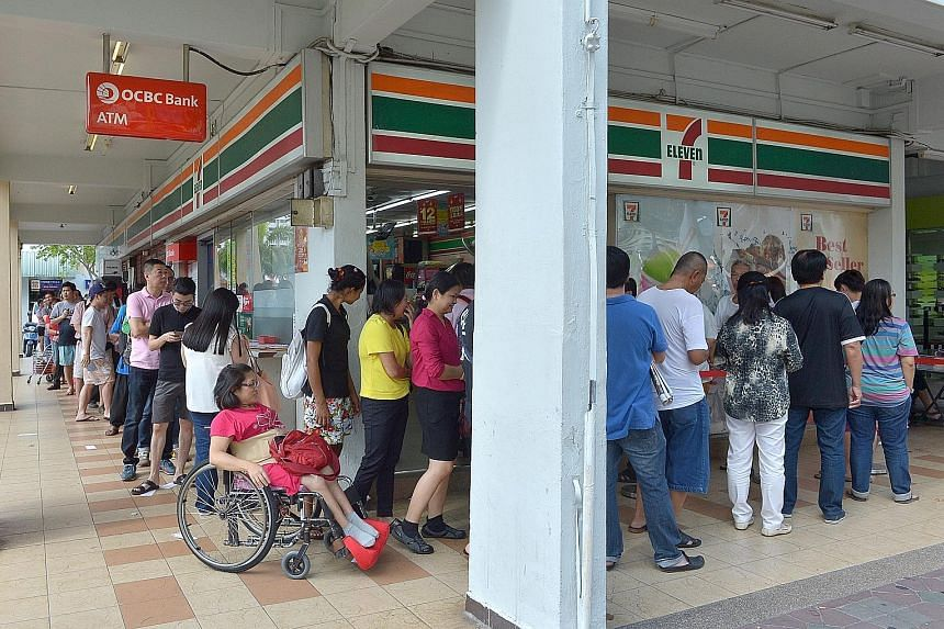 Ms Lucy Ng (in wheelchair), 51, was among the people waiting in line to buy Toto tickets at the 7-Eleven outlet at Block 102 in Yishun Avenue 5 yesterday. Ms Ng had travelled from Bukit Batok with her domestic helper to get a ticket from what is thou
