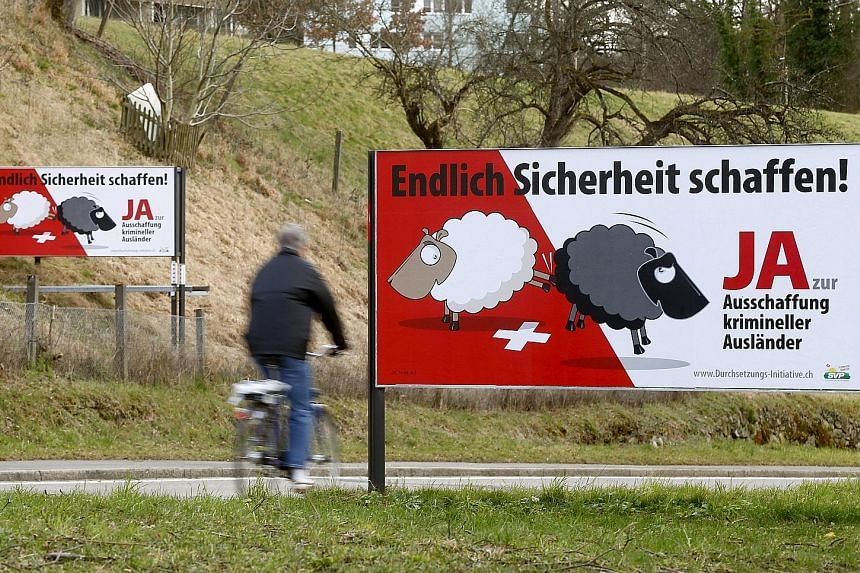 """Posters put up by the Swiss People's Party are displayed on a road in Adliswil, Switzerland. The posters read: """"At last make things safer! Say yes to deportation of criminal foreigners."""" Those opposed to the anti-immigration party's referendum campai"""