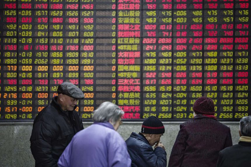 People stand in front of an electronic board displaying share prices at a securities exchange house in Shanghai.