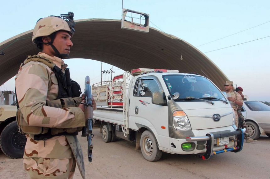 A member of the Iraqi security force stands guard at a checkpoint in Basra province, Jan 15, 2016.