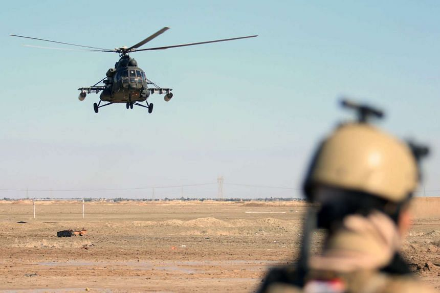A helicopter provides aerial support, during a ground Iraqi military operation to disarm local militias in January 2016.