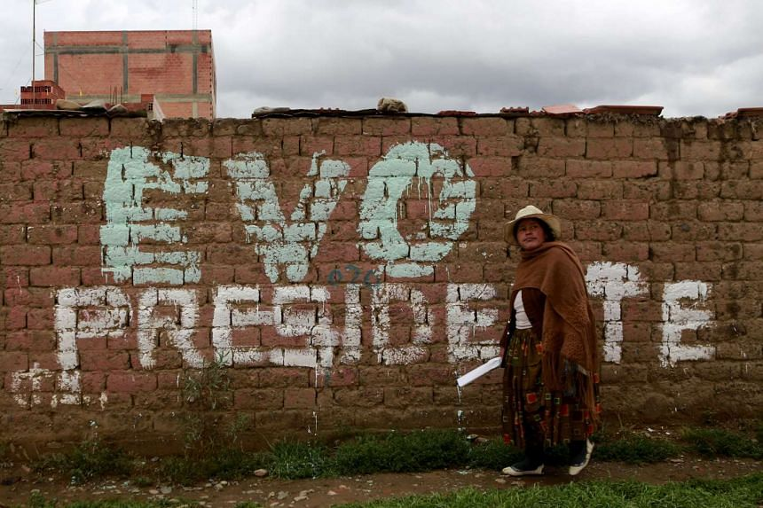 """A woman walks in front of a wall reading """"Evo (Morales) President"""" in El Alto on Feb 15, 2016."""
