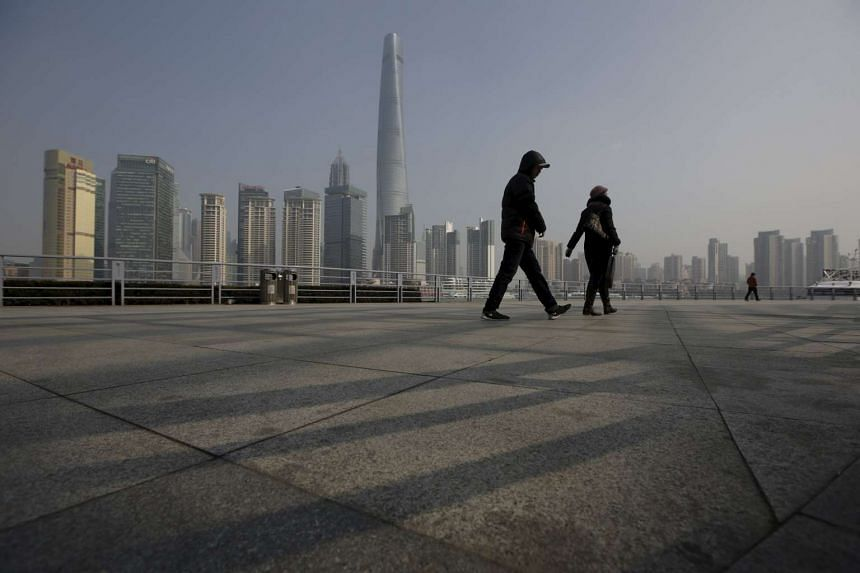 People walk in front of the financial district in Shanghai, China, on Jan 19, 2016.