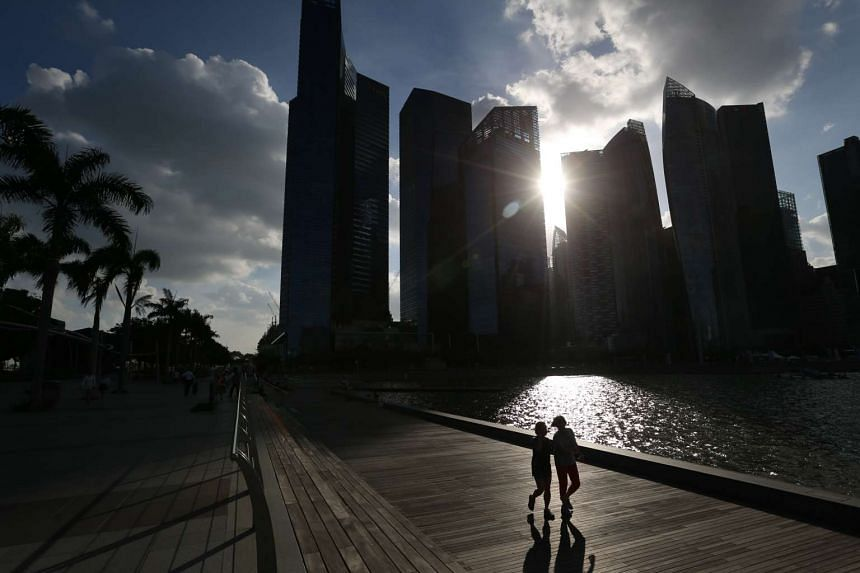 A pair of joggers running along Marina Bay Waterfront Promenade with the Singapore Central Business District skyline silhouetted by the setting sun.