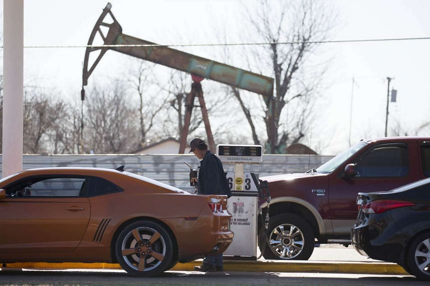 A motorist fills his car with gas at a gas station near an oil field pumping rig.