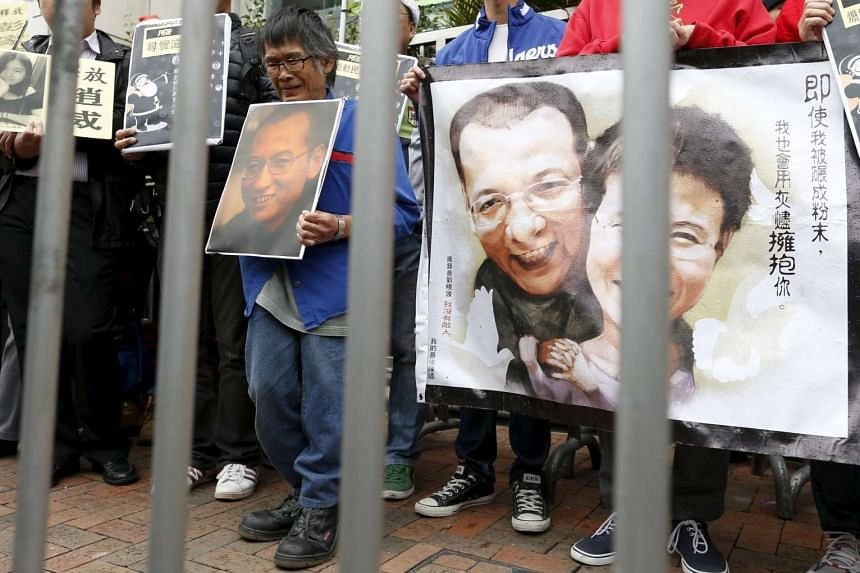 A pro-democracy demonstrator holds a portrait of jailed Chinese Nobel Peace Prize laureate Liu Xiaobo during a protest in Hong Kong on Dec 25, 2015