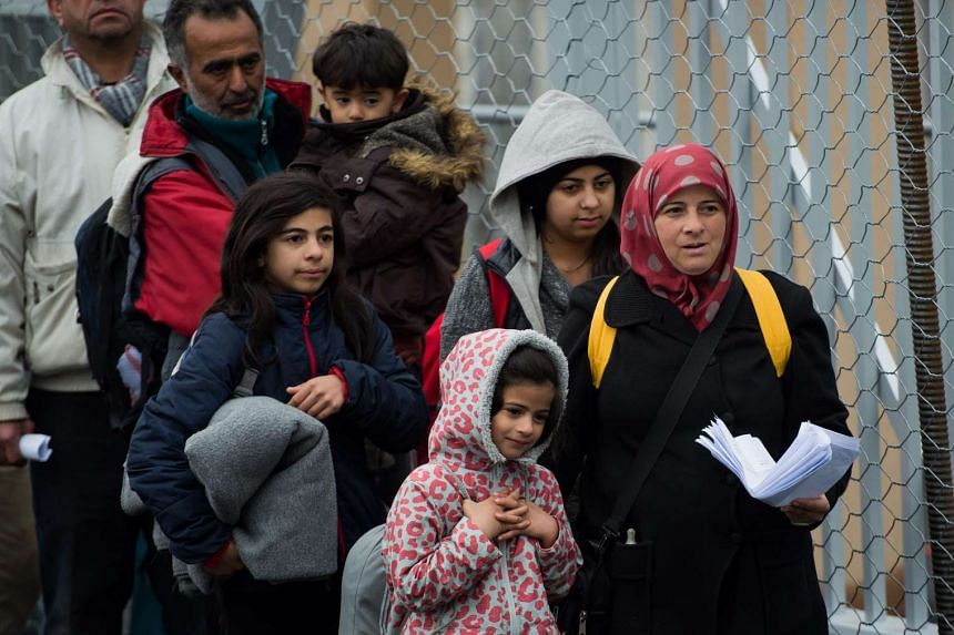 Refugees and migrants line up after crossing the Slovenian-Austrian border on Feb 16, 2016.