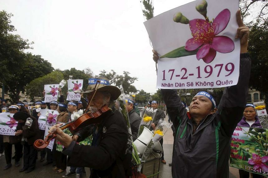 """Musician Ta Tri Hai (centre) plays the violin as anti-China protesters hold placards which read """"People never forget 17th February, 1979"""" in Hanoi, on Feb 17, 2016."""