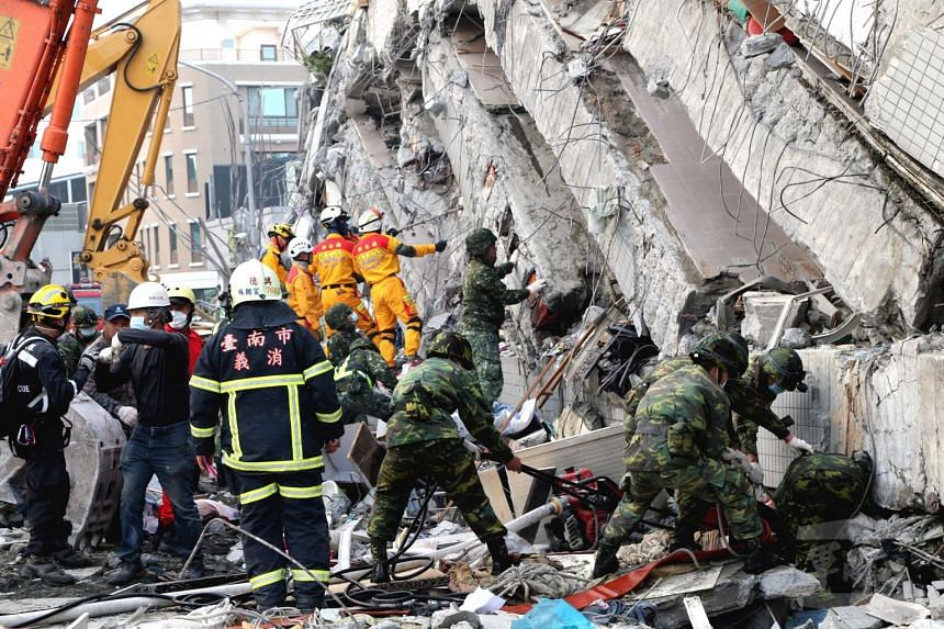 Workers clearing up the remains of a collapsed buiding in Tainan City, Taiwan.