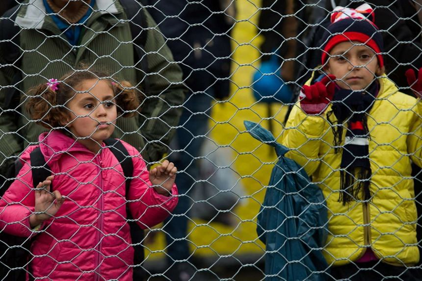 Migrant children line up along a fence after they crossed the Slovenian-Austrian border.