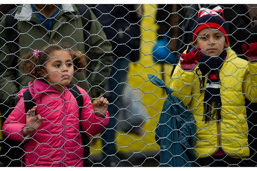 Refugees and migrants children walk along a border fence after they crossed the Slovenian-Austrian border, near the village of Spielfeld, Austria on Feb 16, 2016.