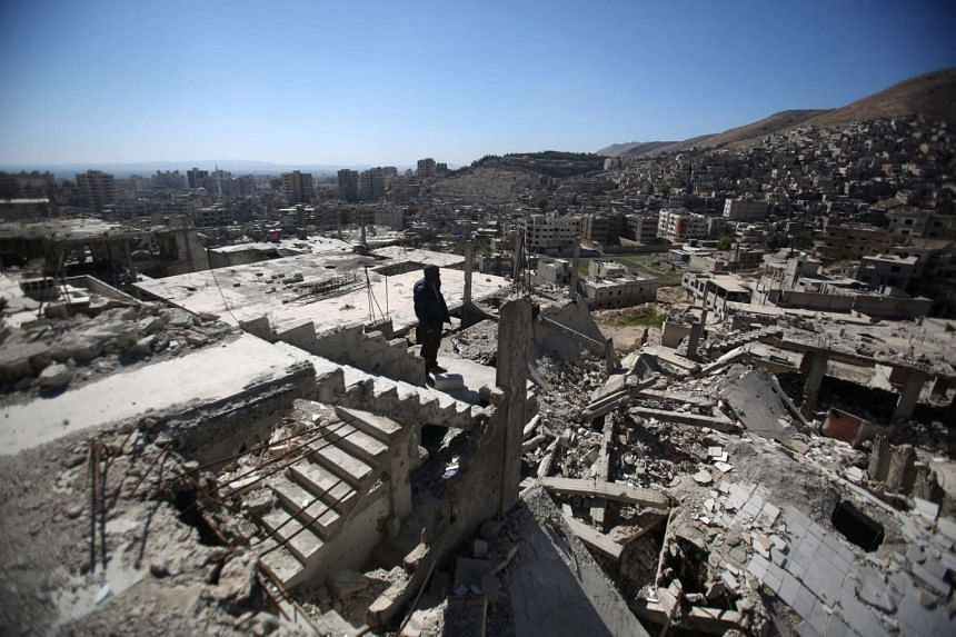 A Syrian man stands on top of a damaged building overlooking the Esh Al-Warwar neighbouhood in Damascus, Syria.