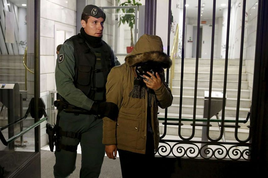 A suspect is led away by a Spanish Civil Guard officer during a raid at ICBC headquarters in Madrid.