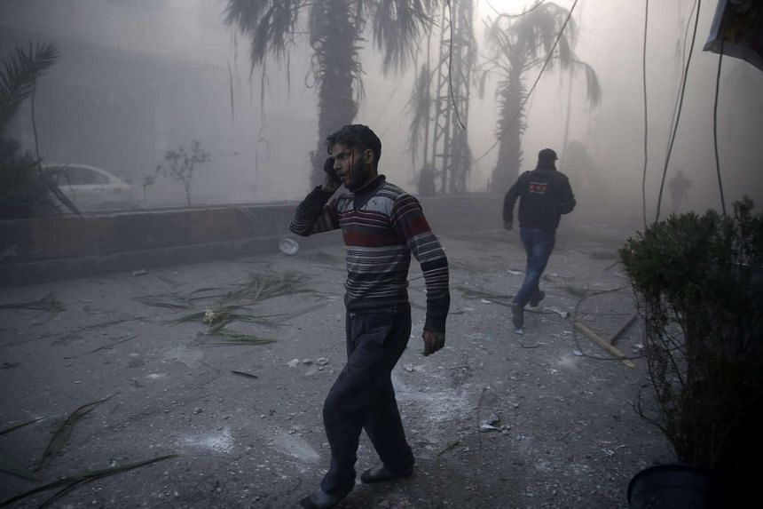 A wounded man walks out of a dust cloud following reported airstrikes in a rebel stronghold east of the Syrian capital Damascus, in Sameer Al-Doumy's photo.