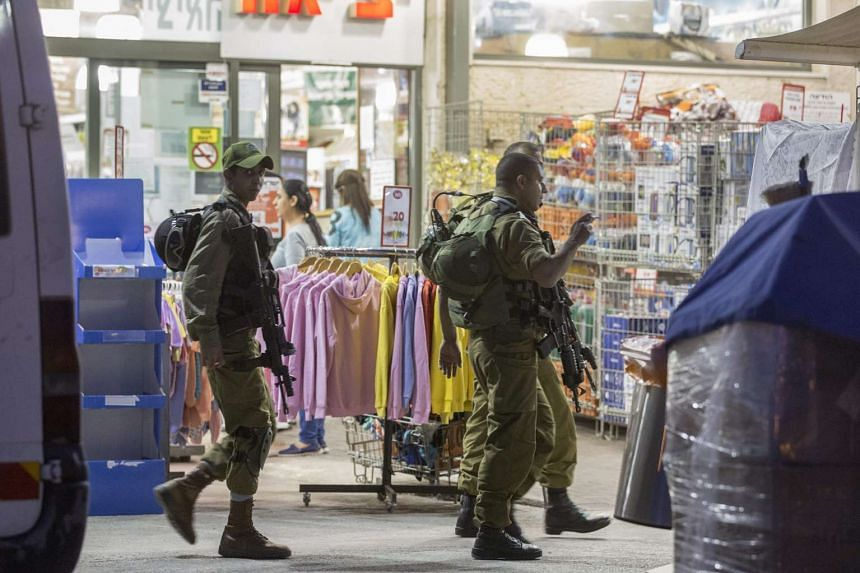 Israeli soldiers outside a supermarket where a two Israelis were stabbed,  in the Shar Binyamin Industrial Area in Jerusalem on Feb 18, 2016.