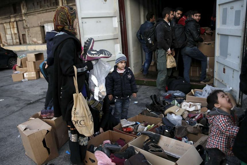 Refugees and migrants search for clothing and shoes gathered by volunteers at the port of Piraeus, near Athens, Greece on Feb 19, 2016.