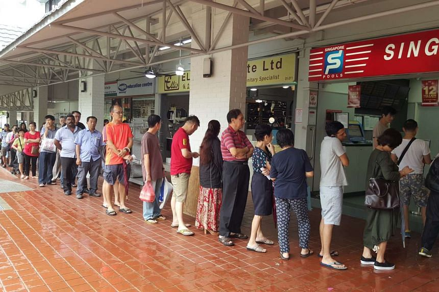 People queueing to buy tickets at a Singapore Pools outlet at Block 211, Hougang Street 21, at 4.30pm on Friday.