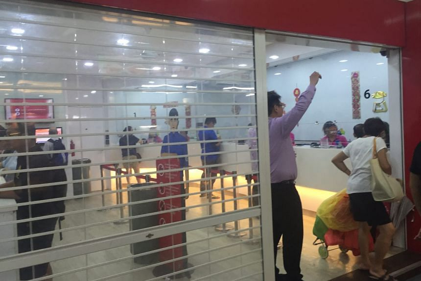 The final few punters buying their tickets before the shutters close at 9pm at a Choa Chu Kang Singapore Pools outlet.