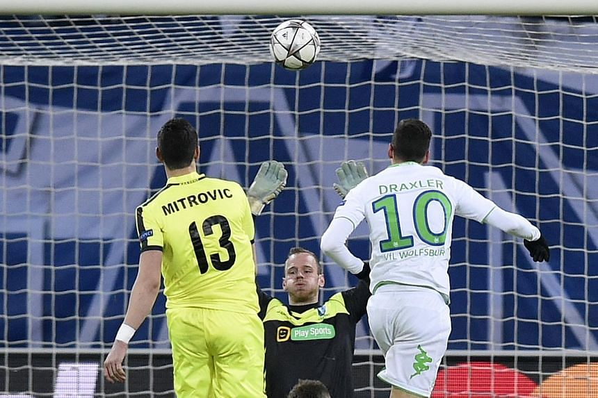 Wolfsburg's midfielder Julian Draxler scores his second with a well-executed chip over Gent's goalkeeper Matz Sels. Wolfsburg won the Champions League last 16 first leg 3-2.
