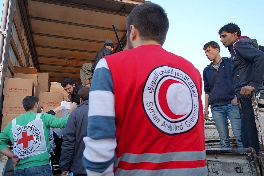 The Syrian Arab Red Crescent and the International Committee of the Red Cross distributing food aid in a buffer zone on the edge of Moadamiyeh, a city under siege in Syria, earlier this month.