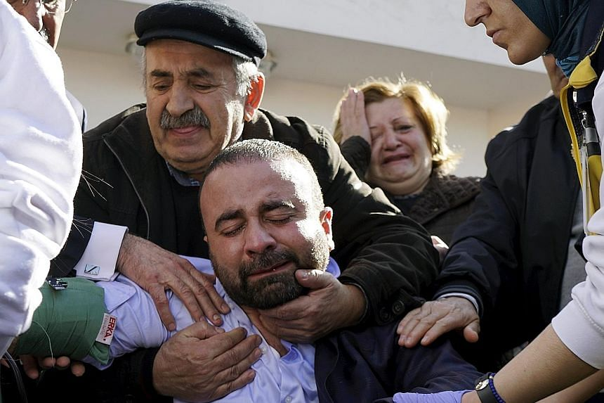Grief-stricken family members of some of the car bombing victims outside a morgue in Ankara yesterday.