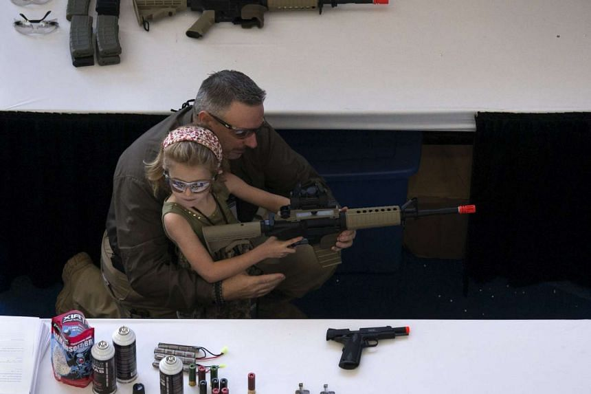 A man shows a girl how to hold an airsoft gun during the NRA Youth Day in Texas.